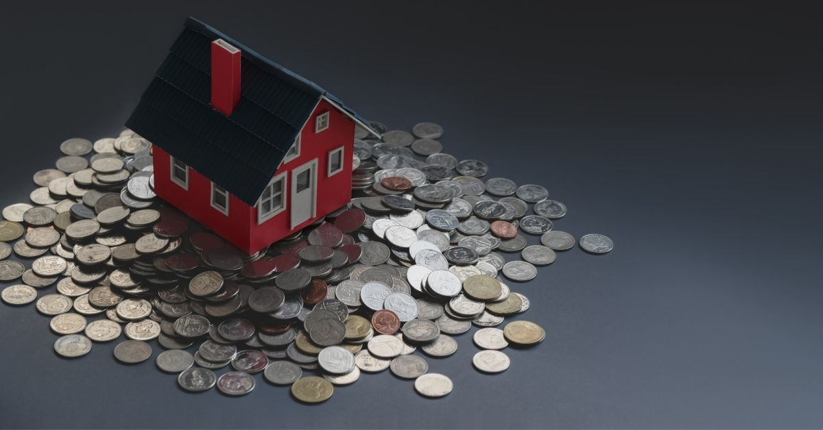 A toy house is surrounded by coins. The CFPB released a five-year TRID assessment that found mixed results for lenders and borrowers.
