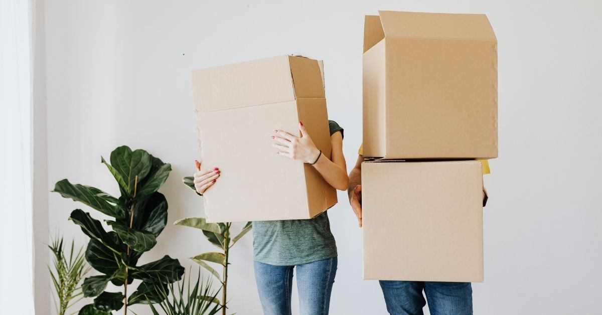 Two people are carrying moving boxes into a new home. Homebuyers have adapted well to eSignings and remote closings during the pandemic.