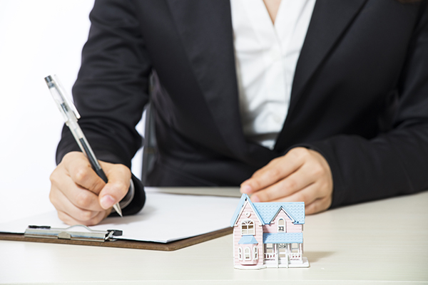 A man writes on a notepad with a tiny model of a house in the foreground. DocMagic is offering clients an automatic audit of lenders' NMLS numbers. (Shutterstock)